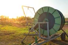 Jordbruks- vattenrörledning på lantgården med solnedgång arkivfoto