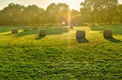 Jordbruksmarkäng med sugrörbalen på solnedgången Franska Brittany royaltyfri fotografi