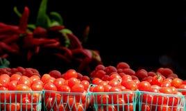 Jordbruksprodukter för körsbärsröda tomater i små korgar Royaltyfri Bild