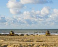 Jordflyttkarlar som arbetar i deras utrustningmaskiner på stranden för underhåll som flyttar sanden arkivfoton