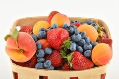 Jordgubbar aprikors, blåbär, persika i korgen som isoleras på Arkivbild