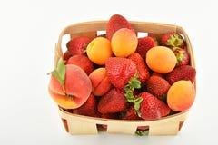 Jordgubbar, aprikors och persika i träkorgen som isoleras på wh Royaltyfri Bild