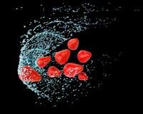 Jordgubbar bevattnar in färgstänk Arkivfoton