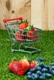 Jordgubbar i en shoppingvagn royaltyfri fotografi