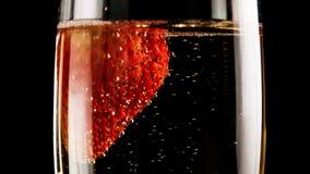 Jordgubbar i ett exponeringsglas av champagne Arkivfoto