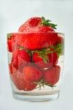 Jordgubbar i ett exponeringsglas med vatten Arkivbild