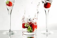 Jordgubbar i ett exponeringsglas som fylls med vatten Royaltyfri Foto