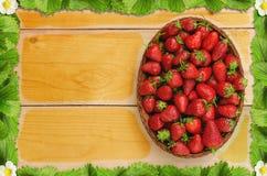 Jordgubbar i korg på trätabellen med en ram av jordgubben lämnar och blommar - sikt för fågelöga arkivbild