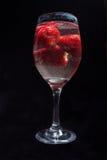 Jordgubbar i vinexponeringsglas med vatten fotografering för bildbyråer