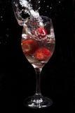 Jordgubbar i vinexponeringsglas med vatten royaltyfria bilder