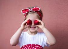 Jordgubbar - lycklig flicka med jordgubbar arkivfoton