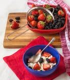 Jordgubbar med gräddost i blåttplatta på köktablen Royaltyfri Bild
