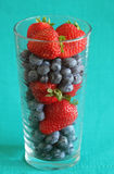 Jordgubbar och blåbär i ett högväxt exponeringsglas Royaltyfria Bilder
