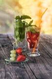Jordgubbar och druvor på en steknål på den glass bakgrunden med jordgubbe- och druvadetoxen dricker på en trätabell på en solig d Arkivfoton