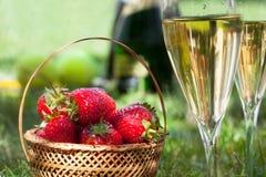 Jordgubbar och exponeringsglas med champagne Arkivfoton