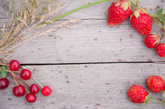 Jordgubbar och körsbär med gräs på trä Fotografering för Bildbyråer