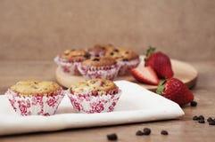 Jordgubbar och muffin för chokladchip, wood bakgrund fotografering för bildbyråer