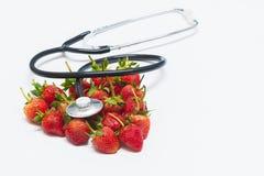 Jordgubbar och stetoskop på vit bakgrund royaltyfria foton