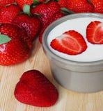 Jordgubbar som är hela och skivas med grekisk yoghurt på träbakgrund arkivfoton