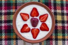 Jordgubbar som är ordnade i en bunke av yoghurt royaltyfria bilder