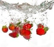Jordgubbar som faller in i vatten Arkivfoto