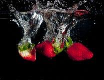 Jordgubbar som plaskar in i vatten Arkivfoton