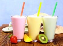 Jordgubbe-, mango- och kiwismoothie med feriebakgrund Royaltyfria Foton