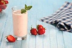 Jordgubbe med yoghurt i ett exponeringsglas på en träbakgrund arkivfoto