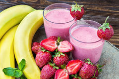 Jordgubbe- och banansmoothie i exponeringsglaset nya jordgubbar Arkivbilder