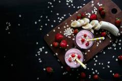 Jordgubbe- och banansmoothie i exponeringsglaset på svart bakgrund Arkivfoton