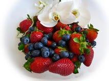 Jordgubbe och blåbär på den vita plattan med orkidér royaltyfri foto