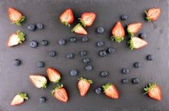 Jordgubbe och blåbär på mörk bakgrund, bästa sikt royaltyfri foto