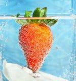 Jordgubbe och druvor i vatten med bubblor, coctail Arkivbild