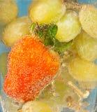 Jordgubbe och druvor i vatten med bubblor, coctail Royaltyfri Fotografi