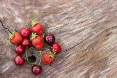 Jordgubbe och körsbär på trätabellen Arkivfoto