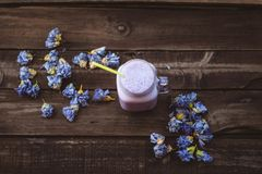 Jordgubbe- och tranbärsmoothie med torkade blommor på en trätabell fotografering för bildbyråer