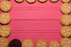 Jordgubbe-smaksatte kräm-fyllda kakor samman med chokladkakan fotografering för bildbyråer