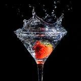 Jordgubbe som plaskar in i exponeringsglas av martini Fotografering för Bildbyråer