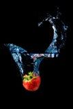 Jordgubbe som plaskar in i vatten på black Arkivfoto