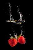 Jordgubbe som plaskar in i vatten på black Fotografering för Bildbyråer