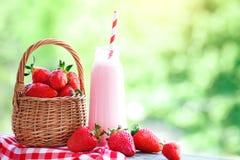 Jordgubbecoctail eller milkshake i en krus, korg med jordgubbar på en picknick, sund mat för frukost och mellanmål Arkivbilder