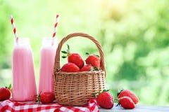 Jordgubbecoctail eller milkshake i en krus, korg med jordgubbar på en picknick, sund mat för frukost och mellanmål Arkivbild