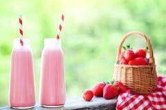 Jordgubbecoctail eller milkshake i en krus, korg med jordgubbar på en picknick, sund mat för frukost och mellanmål Royaltyfria Bilder