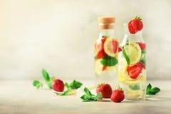 Jordgubbedetoxvatten med mintkaramellen, citron på grå bakgrund Citrus lemonad Ingett vatten för sommar frukt kopiera avstånd arkivbilder