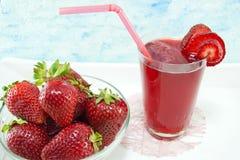 Jordgubbefruktsaft och nya jordgubbar tjänade som på plattan Arkivfoton
