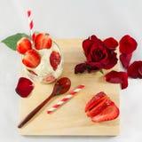 Jordgubbeglass, rosblomma och sked på träbrädekomp Arkivbild