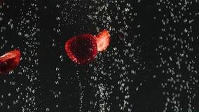 Jordgubbehalvor som faller in i vattnet med bubblor på svart bakgrund Nya bär i vattnet Organiskt b?r stock video