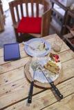 Jordgubbekaka på trätabellen med kniven, gaffel, minnestavlaPC Royaltyfri Fotografi