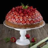 Jordgubbekakan med vaniljkräm dekorerade med den nya jordgubbar och mintkaramellen på en trätabell Svart bakgrund arkivbilder