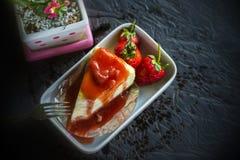 Jordgubbekräppkaka som överträffar frukter och häller jordgubbedriftstopp på den keramiska plattan på den wood tabellen Royaltyfria Bilder